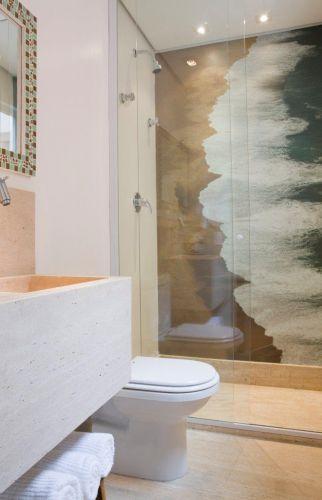 O lavabo ganhou um box e agora serve como banheiro da saleta de leitura no térreo, podendo ser usada como quarto de hóspedes. O piso e a bancada são de mármore travertino romano bruto. A parede também ganhou o laminado com aplicação de uma imagem do mar