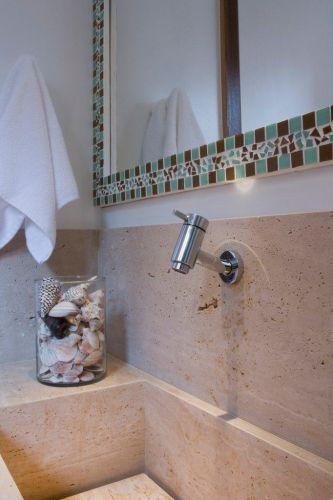 Detalhe da bancada em mármore travertino romano bruto, da Artesamarmo. O espelho com moldura em mosaico torna o espaço mais sofisticado