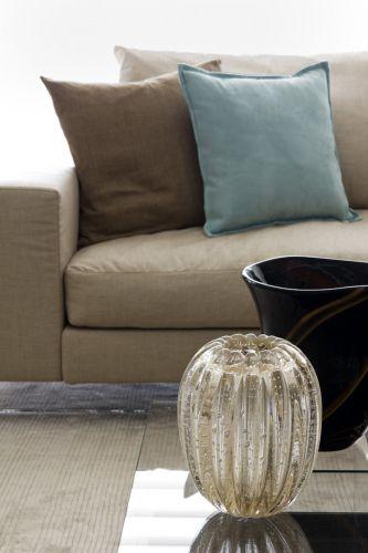 Detalhe dos sofá da Flexform de cor bege - com almofadas coloridas do Empório Beraldin - e da mesa de centro feita de vidro, projetada pelo designer Piero Lissoni, que suporta as peças coloridas de vidro. O projeto de decoração do apartamento no bairro Panamby, em São Paulo, é assinado pela designer de interiores Marília Brunetti de Campos Veiga