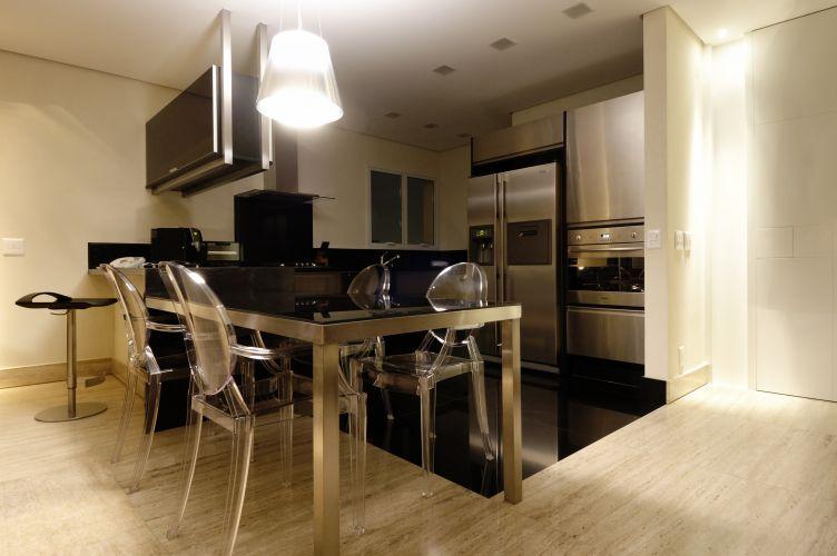 A cozinha integrada no living é demarcada pelo piso revestido com granito preto absoluto da Dimarmo. Em L e com ilha, abriga na parede geladeira, forno e armário em aço escovado. A pia foi instalada na parede da janela e, na bancada, o cooktop. O armário com vidro serigrafado é da Formaplas. A mesa de aço escovado e vidro é como um prolongamento da bancada; cadeiras Louis Ghost, criadas por Philippe Starck para a Kartell, completam a ambientação