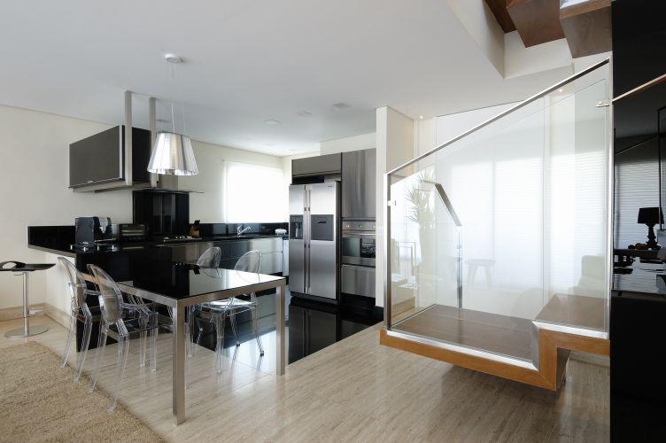 O aço escovado e o vidro, presentes na escada e na cozinha enfatizam o estilo contemporâneo do living