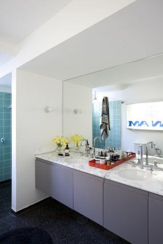 Os azulejos verdes aplicados no banheiro da suíte são originais do imóvel; foram limpos e reassentados na área de chuveiro. O piso é de granilite preto