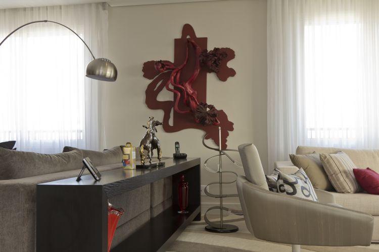Na parede entre o estar e o home theater, escultura de Bia Doria, em vermelho, contrastando com a predominância de tons neutros no mobiliário