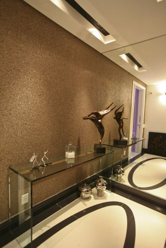 O hall social recebeu, no piso, porcelanato preto recortado na forma oval, enquanto o papel de parede (da Wallpaper) imita a mica, e tem aspecto de