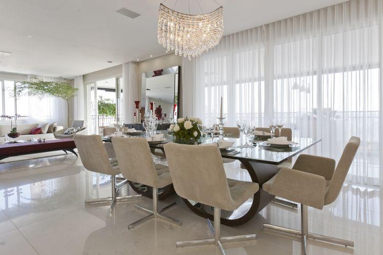 As cadeiras da sala de jantar, em veludo claro, destacam os pés da mesa, modelo Sui Generis, assinada por Sergio Fahrer e vendida pela Brentwood