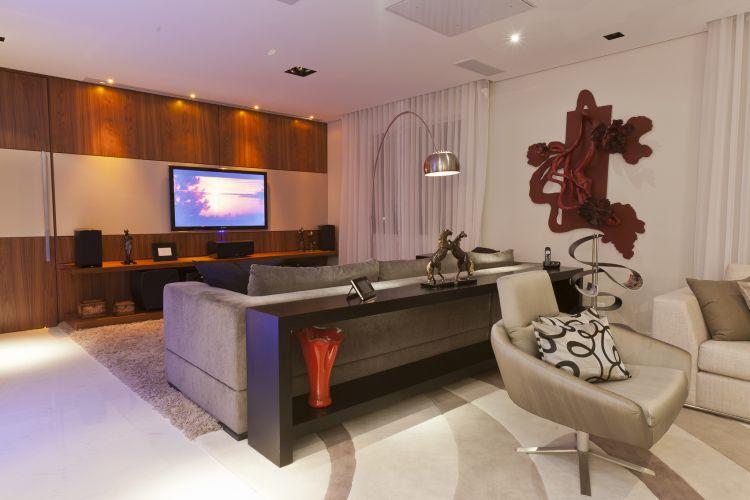Na sala de TV do apartamento decorado por Mayra Lopes, a mesma parede que acomoda a TV foi revestida com madeira em duas cores. O telão do home thetre também fica nesse ambiente, que tem sofá chumbo da Artefacto e luminária modelo Arco, da Dominici