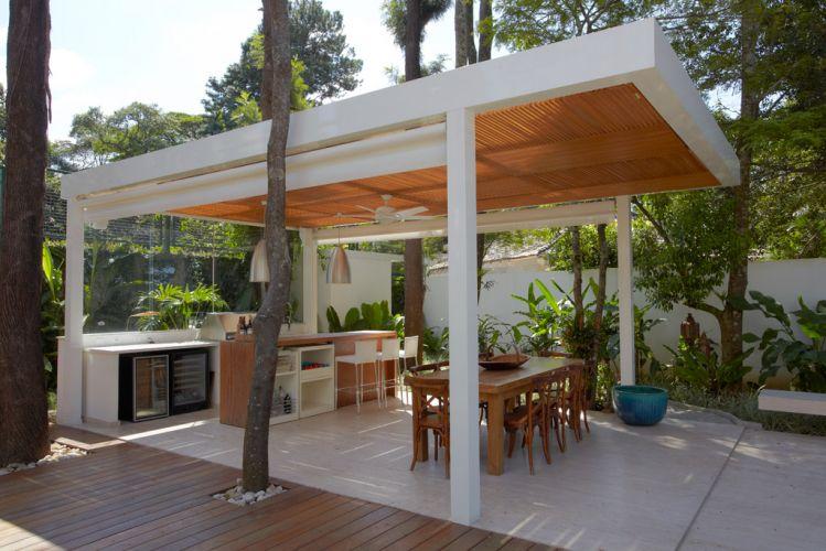 Na casa no bairro do Morumbi, em São Paulo, projeto de Monica Drucker, o gazebo da área de lazer foi executado com perfis de alumínio na cor branca, com fechamento lateral no sistema rollon. Painéis feitos com ripas de madeira cumaru, formando quadrados perpendiculares, proporcionam sombra à cobertura de alumínio e vidro laminado de 10 mm. No primeiro plano, mesa, cadeiras e vasos da L'Oeil. A Iluminação, da Punto Luce, é formada por pendentes de aço inox e lâmpadas Pls na cor amarelo claro