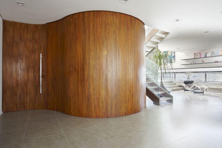 Parede curva original da área social do apartamento de 600 m² reformado pela arquiteta Monica Drucker, localizado na zona este de São Paulo. O volume oculta a caixa de escadas do edifício e era originalmente constituído por paredes ortogonais, agora revestidas com ripas de cumaru de 3 cm de largura