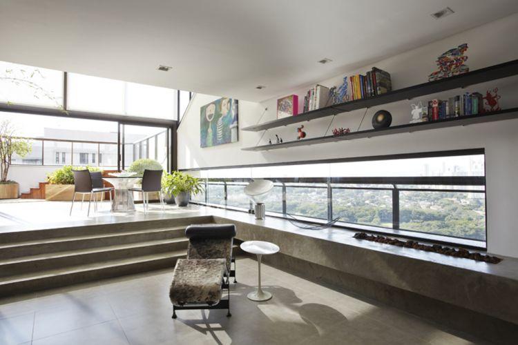 O ambiente com lareira situado junto ao terraço coberto tem janela fita com vista panorâmica para um parque. A bancada, os degraus e o piso são de concreto executados pela Dalle Piage. A chaise Le Corbusier e a mesinha de canto Saarinen completam o ambiente criado pela arquiteta Monica Drucker