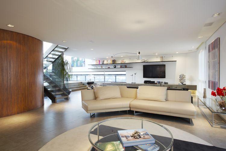 Sala de estar do dúplex reformado por Monica Drucker em São Paulo. A mesa de centro com vidro da Guardian e o sofá da alemã Rolf Benz, revestido em couro bege, são da Forma. O tapete é da By Kami, desenhado pela arquiteta especialmente para este espaço. À esquerda, parede curva revestida com cumaru
