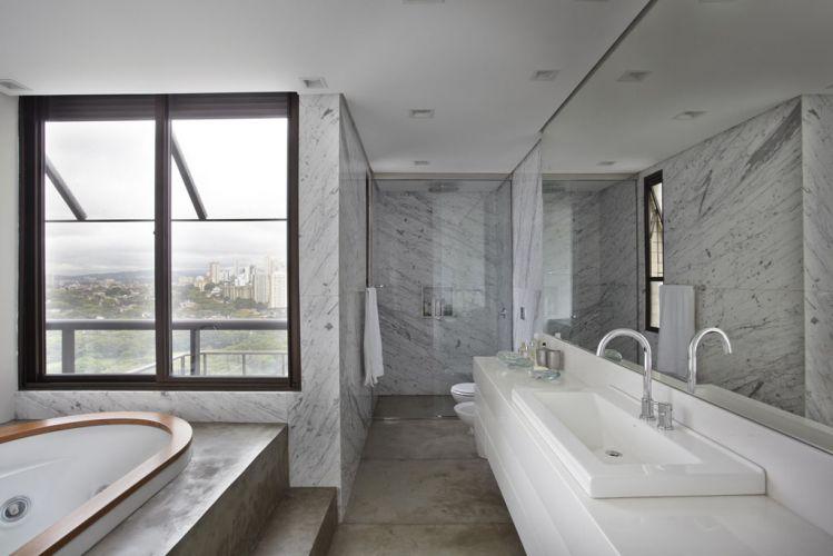 O banheiro da suíte principal tem piso de concreto (executado pela Dalle Piage) e mármore de Carrara nas paredes e branco Thassos na bancada, ambos fornecidos pela Itaarte. Os metais e louças são Deca e a banheira, Jacuzzi. No teto spots embutidos Reka