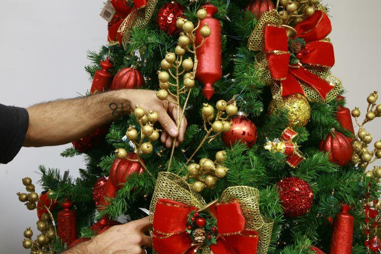 decorar uma arvore de natal : decorar uma arvore de natal:Arremate a parte de cima dos laços com galhos decorados. Finalize com