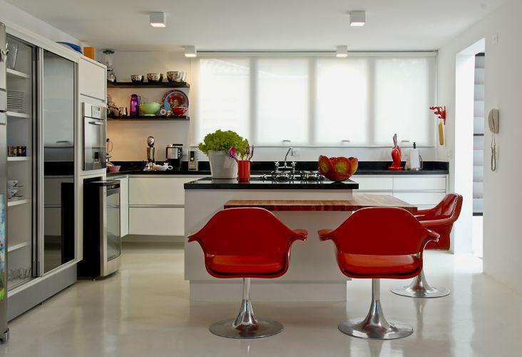 A cozinha planejada foi fornecida pela Bontempo. Destaque para os fornos de parede, embutidos nos armários, e o cooktop na ilha. As cadeiras são do acervo pessoal do proprietário e as cortinas, da Arthur Decoração