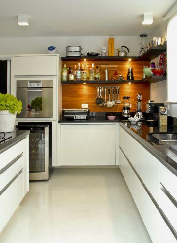 Para suavizar o aspecto clean dos materiais frios e rígidos da cozinha, conferindo calor o ambiente, Neza Cesar revestiu uma das paredes com madeira clara