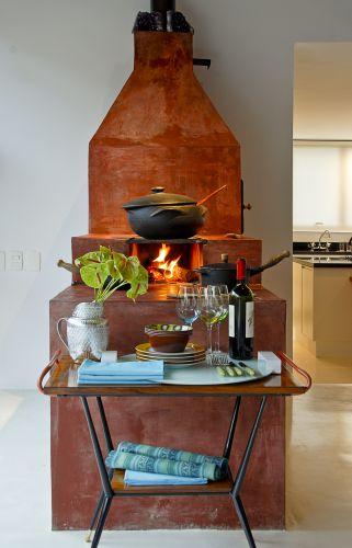 A mesinha vintage do cliente, que se alinha perfeitamente com o fogão de lenha, serve de apoio para o serviço de cozinha. O diálogo entre a delicadeza da peça e a rusticidade do fogão resume o espírito da proposta de interiores da casa