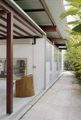 Corredor externo lateral, oposto à varanda principal, por onde também se pode entrar nas suítes e demais cômodos. Outro recurso que garante uma boa circulação de ar