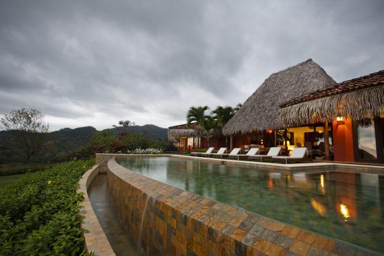 A piscina da casa da família Ewing na Costa Rica usa ladrilhos brasileiros em seu revestimento e está ao lado da sala de estar da residência, formando uma grande e agradável área de lazer