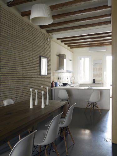 O chão do loft de 120 m² em Barcelona é revestido por uma fina camada de concreto colorido por um cinza muito escuro e luminoso. A cozinha, por sua vez, exibe janelas grandes e uma porta com painéis de vidro que se abre para um pequeno balcão voltado para a rua