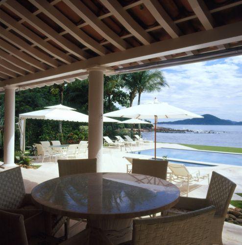 No terraço, a mesa com tampo de mosaico de mármore e as poltronas de junco, todos da Armando Cerello, compõem um ambiente sombreado