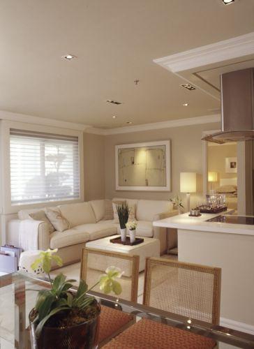 Vista a partir do ambiente de jantar mostra o estar e a cozinha americana e, ao fundo, a porta de acesso à suíte principal. A combinação de tonalidades neutras confere sofisticação ao conjunto