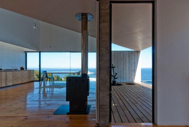 Vista a partir do quarto do térreo mostra os espaços integrados de estar, com lareira, jantar e cozinha, todos com vistas para o mar
