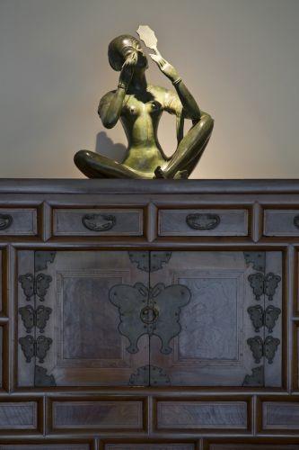 Sobre o móvel de madeira trazido da Coreia, a escultura em bronze, original de Penang, uma Ilha na Malásia