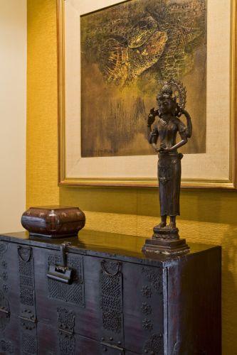 Antiga cômoda coreana com certificação de originalidade, valorizada por sua ferragem decorativa, bastante apreciada na região; e caixa laqueada tradicional coreana, ambos adquiridos em Seul. Duas peças indonésias: escultura de deusa hindu, comprada em Bali, e quadro de Dwidjo Widiyono, de Jacarta
