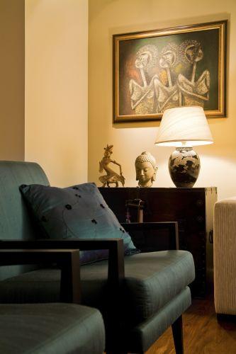 Atrás das poltronas em tafetá de seda da Esfera Móveis, cômoda coreana antiga, certificada, valorizada por sua ferragem decorativa, bastante apreciada na região. A cabeça de Buda de origem indiana foi presenteada por um amigo. Luminária da L'oeil à frente do quadro