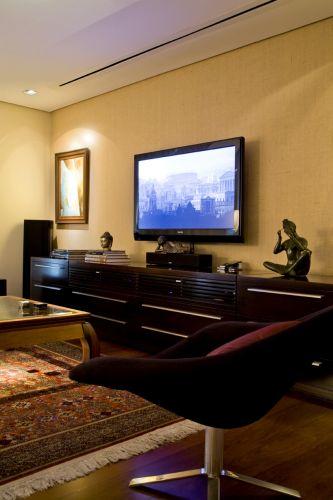 A parede onde está a TV é em drywall, separando o ambiente do ateliê da esposa