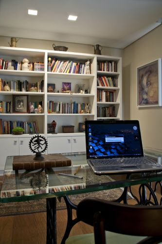 O canto de trabalho da dona da casa é composto pela mesa com a base de uma antiga máquina de costura Singer e tampo de vidro, e a cadeira de madeira
