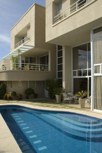 Em primeiro plano, a piscina e a varanda da sala de estar. Ao fundo, a varanda da sala de jantar, no nível superior. As altas aberturas envidraçadas conferem imponência à construção