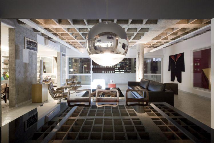 Com a reforma, o imóvel adquiriu configuração de loft. A calha metálica conduz as instalações e a iluminação, planejada para enfatizar os elementos estruturais que servem de contexto para o mobiliário e as obras de arte. Em primeiro plano, sobre a mesa de jantar da Forma, luminária pendente da Lumini