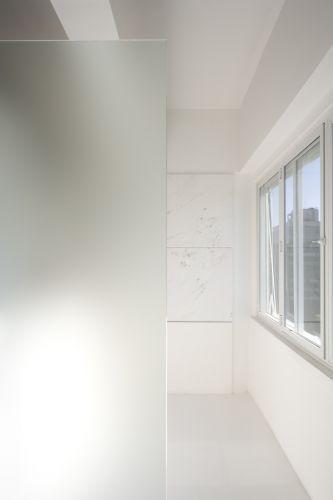 Vista do quarto para o banheiro, instalado no espaço que era de um quarto. A placa de vidro fosco faz a separação do closet