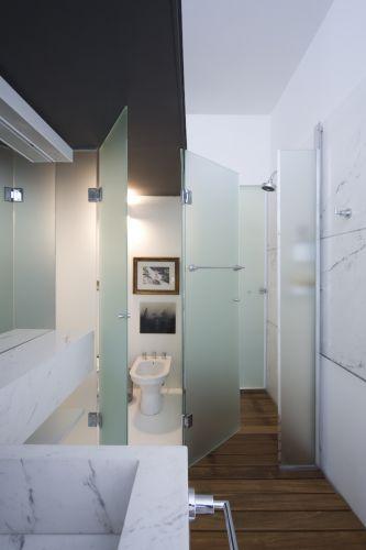 Mármore piguês, epóxi e deck de madeira no piso foram os materiais usados no banheiro da suíte principal. Os boxes de vidro fosco dividem a área do vaso e do chuveiro