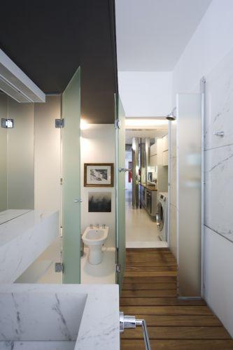 No banheiro da suíte principal, perceba a presença da calha metálica acomodando elétrica, hidráulica e embutindo a iluminação. Ao fundo, mais uma proposta incomum: a ligação com o serviço através da porta no chuveiro