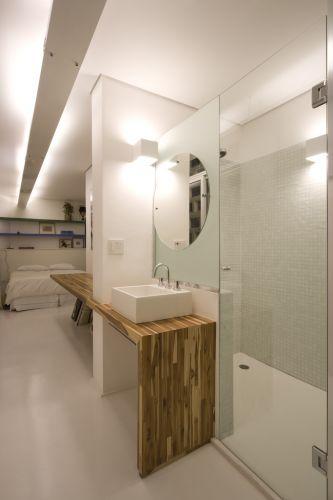 Vista da segunda suíte. A mesma bancada da pia é usada como área de trabalho do lado do dormitório. Vaso e chuveiro são separados por portas envidraçadas