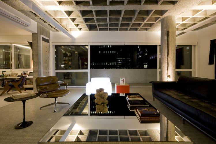 No canto do estar, poltronas Charles Eames, sofá de couro da Dpot. A laje nervurada aparece refletida na mesa de centro com tampo de espelho da Érea