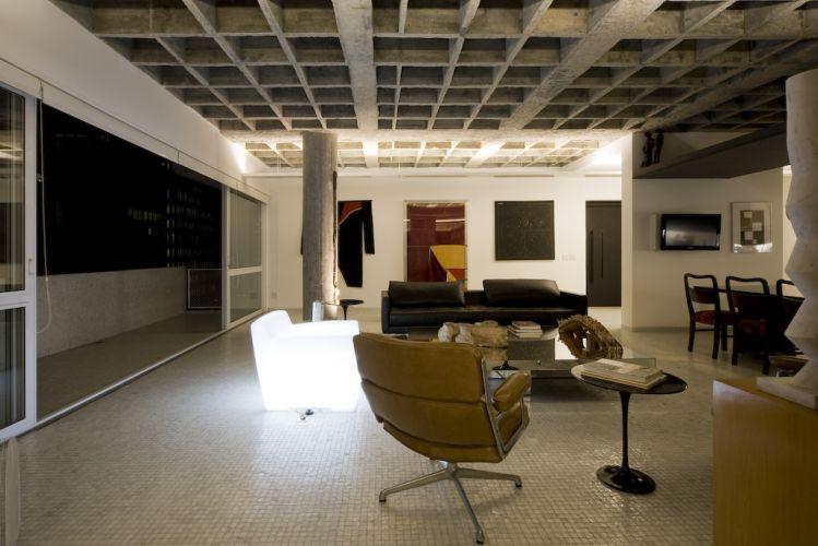 No canto do estar, poltronas Charles Eames, sofá de couro da Dpot, e mesa de centro revestida de espelho da Érea