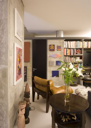 Obras de Leonilson ressaltam-se sobre o concreto do volume e das colunas. O tubo de zinco por onde passam as instalações elétrica e hidráulica contrasta com a rusticidade do concreto