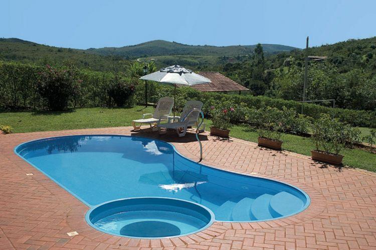 Executada pela Planeta Água, esta piscina de fibra de vidro com degraus e spa recebeu deck de revestimento cerâmico