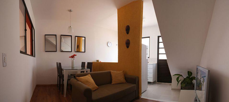 Feita a partir da porta de entrada, a foto mostra o ambiente de estar, nesse caso integrado à cozinha, de onde parte da escada que conduz ao piso superior