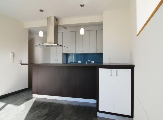 A foto mostra a cozinha americana do loft 203, um dos três com pavimento único. O espaço é equipado com armários, balcão com acabamento tabaco, coifa com design moderno em aço inox e pendentes de luz direcional