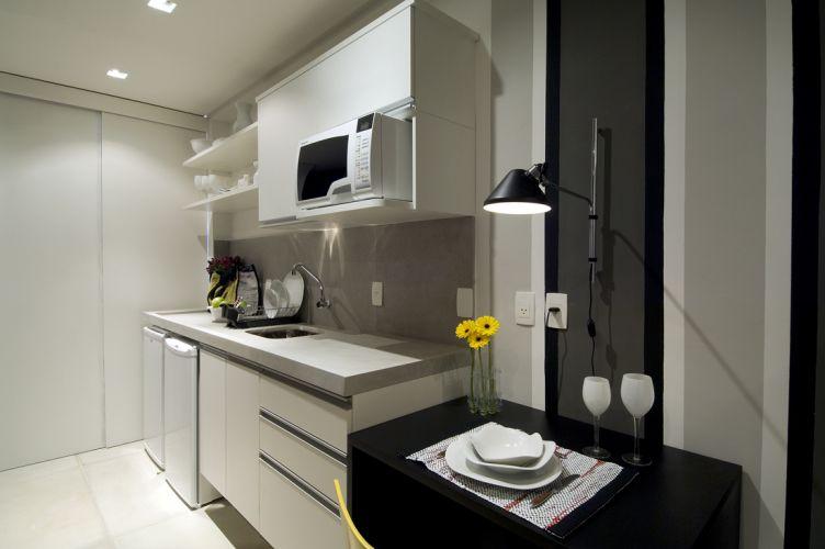 A pequena cozinha foi disposta em uma parede e se separa do serviço pela porta de correr ao fundo. Os armários em laminado melamínico, da Celmar, embutem poucos e primordiais eletrodomésticos, visto que o proprietário pouco para em casa. A bancada em Limestone da Montblanc dá praticidade ao ambiente. Ao lado da pia, Adorno incluiu uma mesa para refeições rápidas