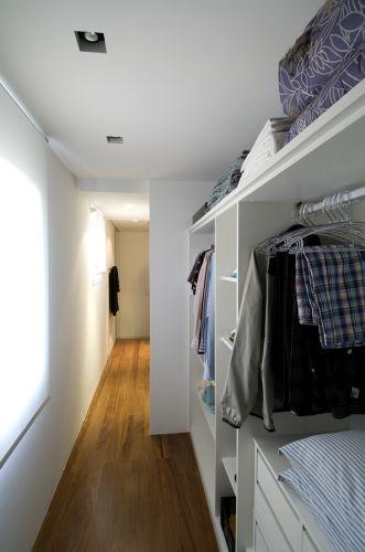 O projeto aproveitou o vão atrás do móvel da cama para colocar os armários do closet, bem iluminado pela luz do sol que entra pelas janelas. Madeira (cumaru) foi aplicada no piso do corredor para aquecer o espaço