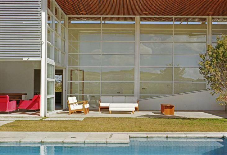 A varanda coberta abriga um espaço de estar aberto, em contraposição à sala com lareira, que pode ser fechada pelas portas de correr