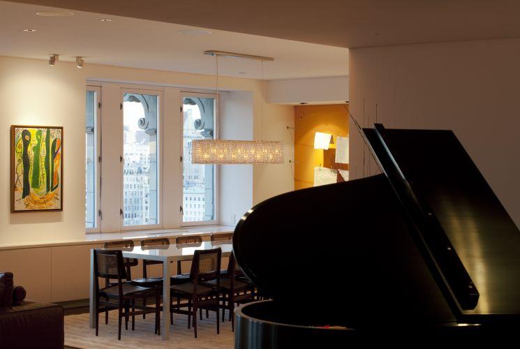 No primeiro plano, o espaço do piano e, ao fundo, o jantar com aberturas para o parque e seu entorno