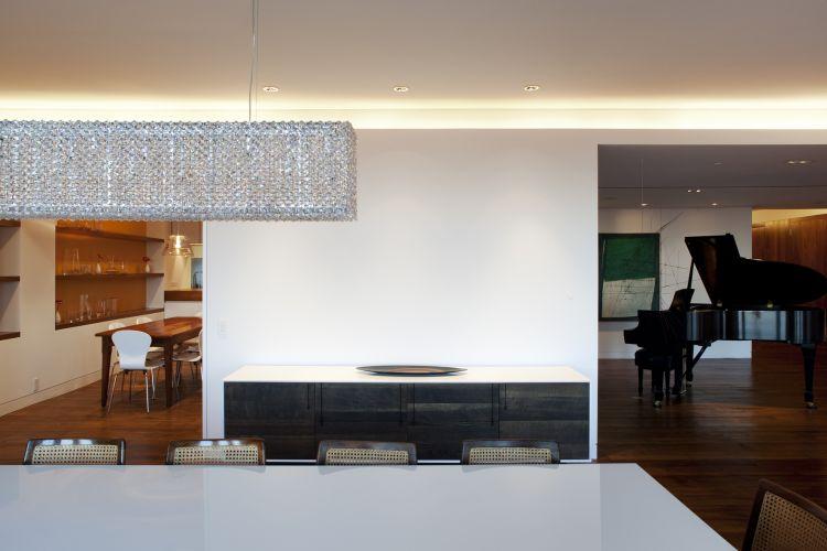 O ambiente de jantar, integrado à copa (à esquerda) e à sala do piano (à direita). Por trás da parede branca fica a despensa