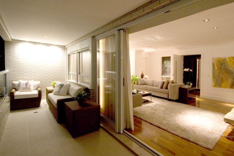 Quando abertas as cortinas, surge a varanda que foi planejada de acordo com as linhas gerais da proposta. Poltronas da Breton, e a iluminação que destaca a textura do revestimento da parede