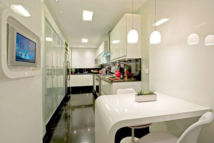 Como a cozinha era estreita, o arquiteto planejou ou um pórtico de madeira ao lado da porta de serviço para formar um pequeno canto de almoço e incorporar a TV. O charme fica por conta da forma arredondada e o acabamento grofato. Sobre a mesa os pendentes da La Lampe
