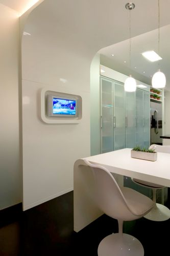Como a cozinha era estreita, o arquiteto planejou ou um pórtico de madeira ao lado da porta de serviço para formar um pequeno canto de almoço e incorporar a TV. O charme fica por conta da forma arredondada e o acabamento grofato. Sobre a mesa os pendentes da La Lampe. Destaque para as cadeiras Tulipa, de Eero Saarinen
